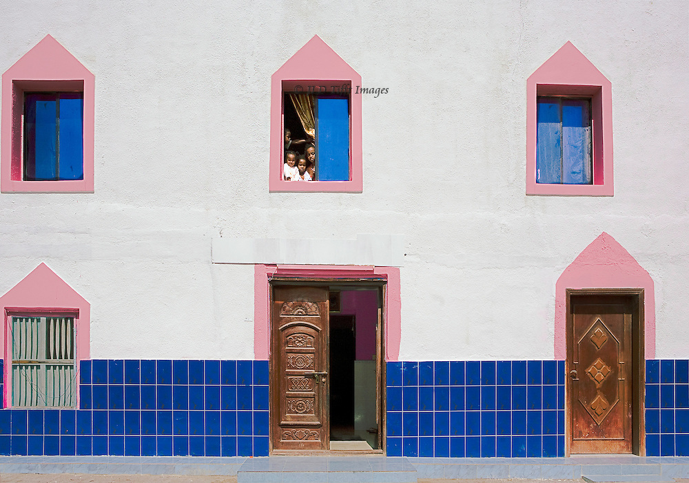 Oman, in the village of Mirbat.  Facade of a brand new house in traditional design.  Open central doorway, carved wooden doors.  Children looking out of upper window.
