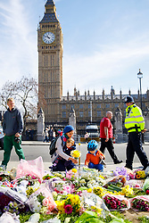 © Licensed to London News Pictures. 25/03/2017. London, UK. A family pay their respects to the victims of Westminster terror attack in Parliament Square, London on 25 March 2017. Photo credit: Tolga Akmen/LNP