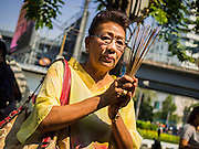 03 FEBRUARY 2015 - BANGKOK, THAILAND:  A woman prays with incense at Wat Hua Lamphong in Bangkok. After months of relative calm following the May 2014 coup, tensions are increasing in Bangkok. The military backed junta has threatened to crack down on anyone who opposes the government. Relations with the United States have deteriorated after Daniel Russel, the US Assistant Secretary of State for Asian and Pacific Affairs, said that normalization of relations between Thailand and the US would depend on the restoration of a credible democratically elected government in Thailand.        PHOTO BY JACK KURTZ
