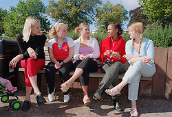 Group of teenage girls sitting talking on park bench,