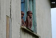 Two young Fijian boys peer from a window.  Mountain village, Vanua Levu island, Fiji.