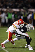 Oakland Raiders wide receiver Brice Butler (12) gets tackled by Kansas City Chiefs defensive back Kurt Coleman (27) as he catches a third down pass for a first down at the Chiefs 11 yard line in the first quarter during the NFL week 12 regular season football game against the Kansas City Chiefs on Thursday, Nov. 20, 2014 in Oakland, Calif. The Raiders won their first game of the season 24-20. ©Paul Anthony Spinelli
