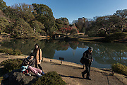 Tokyo, Bunkyo ward, Japan, December 6 2017 - An old man and a young family enjoy a visit of Rikugien Gardens, one of the most beautiful traditional garden in Tokyo.