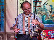 "30 JUNE 2016 - BANGKOK, THAILAND: One of the musicians tunes his two stringed Chinese violin at Chiao Eng Piao Shrine in Bangkok. Chinese opera was once very popular in Thailand, where it is called ""Ngiew."" It is usually performed in the Teochew language. Millions of Chinese emigrated to Thailand (then Siam) in the 18th and 19th centuries and brought their culture with them. Recently the popularity of ngiew has faded as people turn to performances of opera on DVD or movies. There are about 30 Chinese opera troupes left in Bangkok and its environs. They are especially busy during Chinese New Year and Chinese holidays when they travel from Chinese temple to Chinese temple performing on stages they put up in streets near the temple, sometimes sleeping on hammocks they sling under their stage.       PHOTO BY JACK KURTZ"