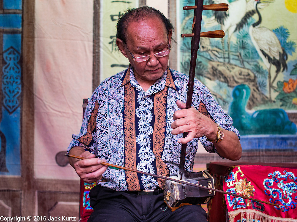 """30 JUNE 2016 - BANGKOK, THAILAND: One of the musicians tunes his two stringed Chinese violin at Chiao Eng Piao Shrine in Bangkok. Chinese opera was once very popular in Thailand, where it is called """"Ngiew."""" It is usually performed in the Teochew language. Millions of Chinese emigrated to Thailand (then Siam) in the 18th and 19th centuries and brought their culture with them. Recently the popularity of ngiew has faded as people turn to performances of opera on DVD or movies. There are about 30 Chinese opera troupes left in Bangkok and its environs. They are especially busy during Chinese New Year and Chinese holidays when they travel from Chinese temple to Chinese temple performing on stages they put up in streets near the temple, sometimes sleeping on hammocks they sling under their stage.       PHOTO BY JACK KURTZ"""