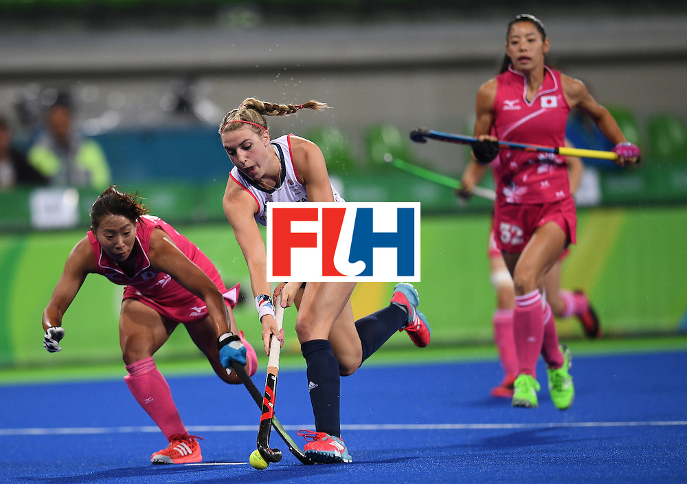 Britain's Lily Owsley (C) tries to get past Japan's Yukari Mano (L) during the women's field hockey Japan vs Britain match of the Rio 2016 Olympics Games at the Olympic Hockey Centre in Rio de Janeiro on August, 11 2016. / AFP / MANAN VATSYAYANA        (Photo credit should read MANAN VATSYAYANA/AFP/Getty Images)