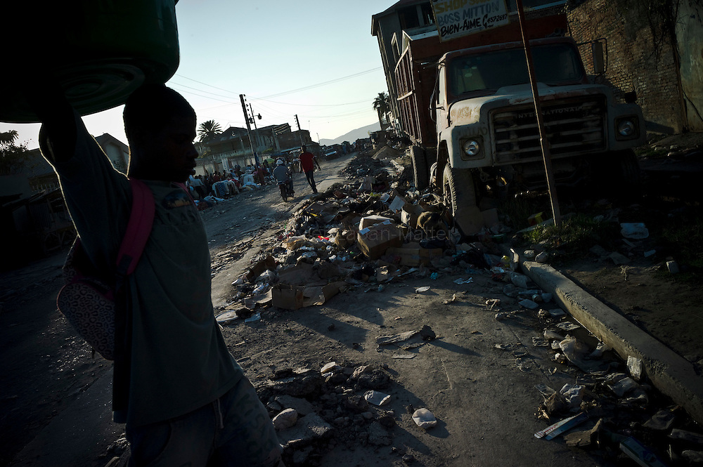 Cholera epidemic, spreading to Haiti last month, finds its source in the Artibonite region, fed by the river of the same name. A man carries a basin, 16 november 2010, in a street of Gonaïves, Artibonite.