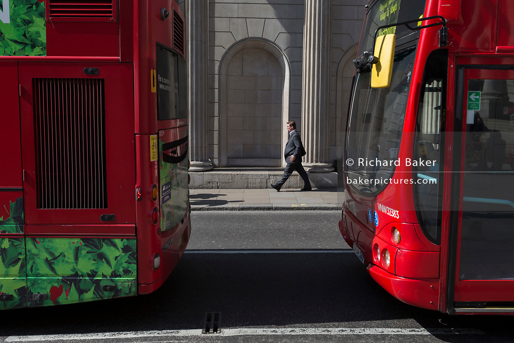 A businessman below the tall pillars of the Bank of England on Threadneedle Street, pass between red London buses, on 10th May 2017, in the City of London, England.