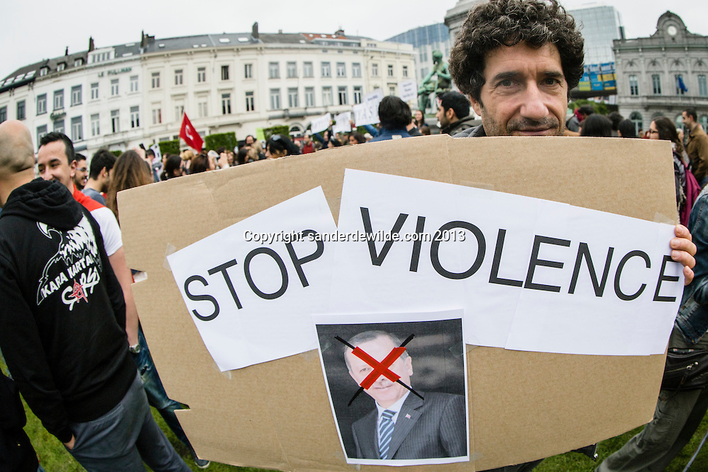Brussel 1st  Juni 2013. A few hundred Turkish Belgiums protested at the European Parliament against Turkish prime minister Erdogan and the use of gas against demonstrators in Istanbul.A man holds a sign saying stop violence and a picture of erdogan crossed.