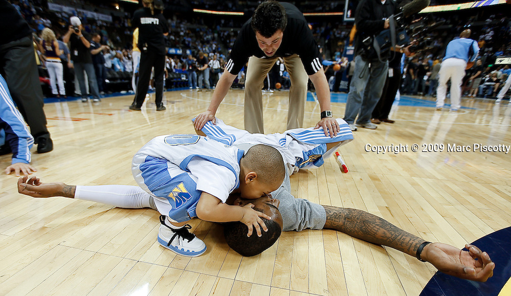 The Denver Nuggets' J.R. Smith gets a good luck kiss on the cheek by Tanner Jones, 3, the son of teammate Dahntay Jones, as Smith stretches out on the floor prior to Game 3 against the Los Angeles Lakers in their NBA Western Conference Finals playoff basketball game at the Pepsi Center in Denver, Co. May 23, 2009. .(Photo by Marc Piscotty / © 2009)
