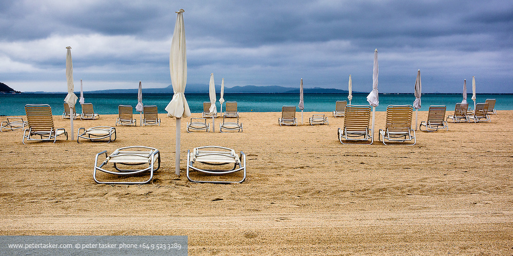 Okuma beach, Okinawa, Japan.  Empty deck chairs at the beginning of a cloudy day.