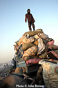 A worker stands atop a pile of sacks that will be transported to recycling facilities at The Stung Meanchey Landfill in Phnom Penh, Cambodia.