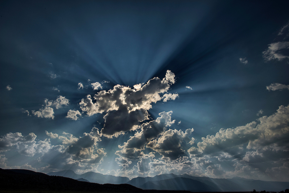 The sun beams shoot through the sky at Mono Lake with the Sierra's in the background.