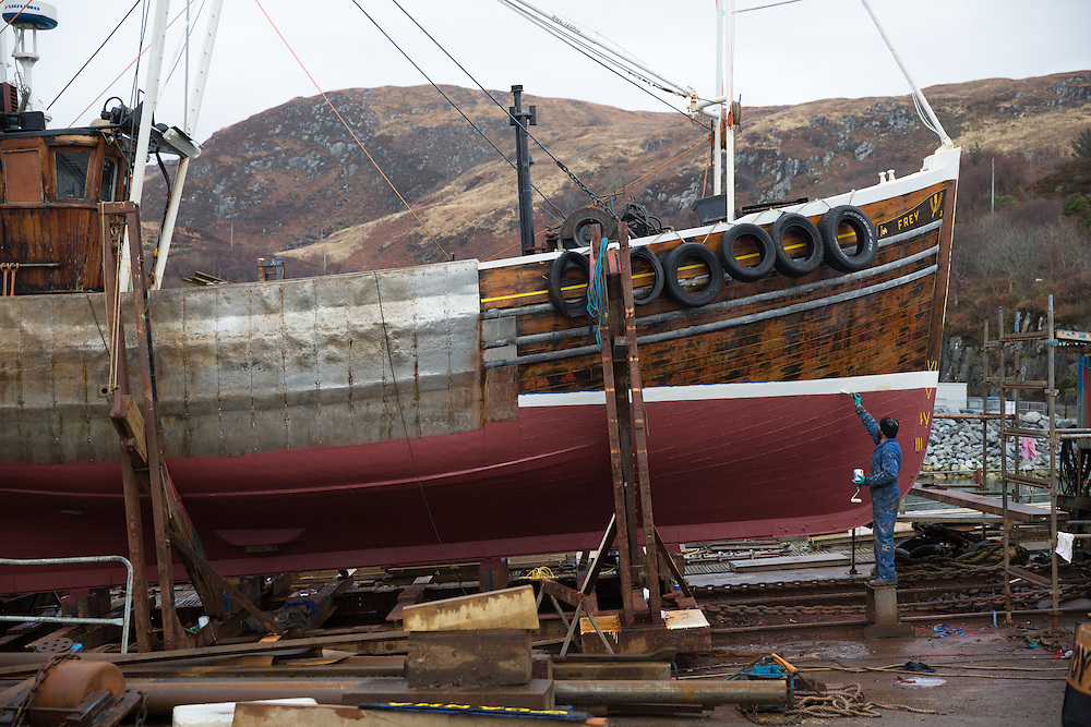 Mallaig Boatyard.  Boatbuilder Robert Nicholson painting the Frey. Picture Robert Perry 9th April 2016<br /> <br /> Must credit photo to Robert Perry<br /> FEE PAYABLE FOR REPRO USE<br /> FEE PAYABLE FOR ALL INTERNET USE<br /> www.robertperry.co.uk<br /> NB -This image is not to be distributed without the prior consent of the copyright holder.<br /> in using this image you agree to abide by terms and conditions as stated in this caption.<br /> All monies payable to Robert Perry<br /> <br /> (PLEASE DO NOT REMOVE THIS CAPTION)<br /> This image is intended for Editorial use (e.g. news). Any commercial or promotional use requires additional clearance. <br /> Copyright 2014 All rights protected.<br /> first use only<br /> contact details<br /> Robert Perry     <br /> 07702 631 477<br /> robertperryphotos@gmail.com<br /> no internet usage without prior consent.         <br /> Robert Perry reserves the right to pursue unauthorised use of this image . If you violate my intellectual property you may be liable for  damages, loss of income, and profits you derive from the use of this image.