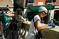 Manutenzione del ponte di Rialto ad opera di una restauratrice. L'elevato numero di turisti comporta una maggiore necessità di restauri.
