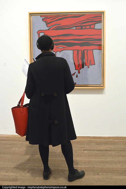 """© Licensed to London News Pictures. 18/02/2013. London, UK A woman stands in front one of the """"brush stroke"""" series paintings .Press view for Tate Modern's """"Lichtenstein: A Retrospective"""". It is the first major Lichtenstein retrospective for twenty years, bringing together 125 of the artists most definitive paintings. The exhibition is open to the public from 21 February -  27 May 2013.  Photo credit : Stephen Simpson/LNP"""