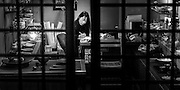 A business woman in a small shop set amongst suburban homes, - on a cold Kyoto winters night.