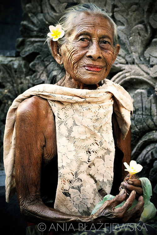 Indonesia, Bali. Portrait of a beautiful elderly balinese lady selling flowers in Pura Beji temple in Sangsit.