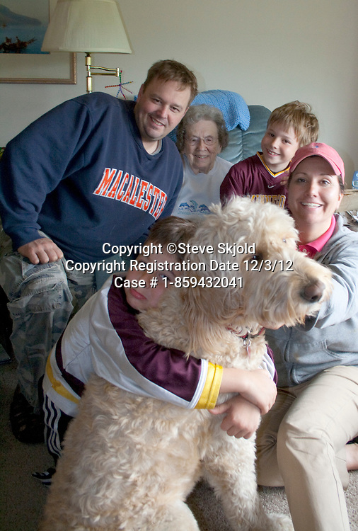 Great grandmother age 95 enjoying three of four generations and Gunnar the family Goldendoodle dog Battle Lake Minnesota MN USA