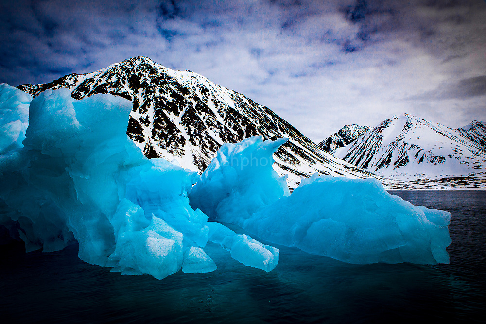 Iceberg in Magdalenefjorden, and 8km long, 5km wide fjord on the west coast of Spitsbergen, in the Arctic archipelego of Svalbard. Large cruise ships regularly enter the fjord. However, heavy fuel oil, which is used in many ships, is banned in Magdalenefjorden. However, Magdalenefjorden is regarded as having being sacrificed to tourism to protect other areas of Svalbard.