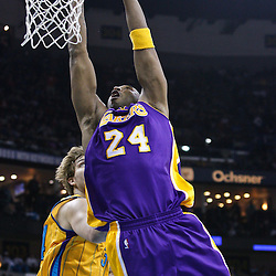 February 5, 2011; New Orleans, LA, USA; Los Angeles Lakers shooting guard Kobe Bryant (24) dunks over New Orleans Hornets center Aaron Gray (34) during the first quarter at the New Orleans Arena.   Mandatory Credit: Derick E. Hingle
