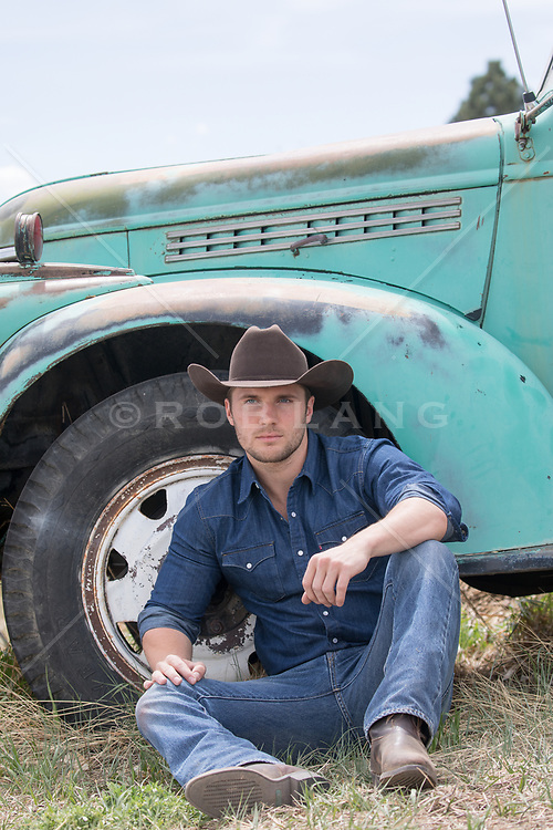 sexy cowboy sitting against a vintage truck