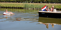 Honselersdijk, 1 augustus 2013.<br /> Jongen in zwemband, voortgetrokken door bootje met Nederlandse vlag<br /> ANP COPYRIGHT MARTIJN BEEKMAN