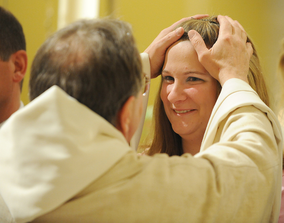 Norbertine Fr. Tim Shillcox, pastor of Our Lady of Lourdes Parish in DePere, Wis., anoints Amy DeBroux with the sacred chrism during the Easter Vigil in 2009. (Sam Lucero photo)