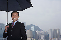 Portrait of business man with umbrella smiling