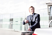 Portrait of attractive businessman putting his suitcase on a car trunk