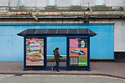 A passer-by walks past a bus shelter featuring Indian food and Go Compare insurance plus a blue hoarding outside a closed entertainment venue in Dartford, on 3rd October 2019, in Dartford, Kent, England. Voters in Dartford voted 64% in favour of Brexit during the 2016 referendum.