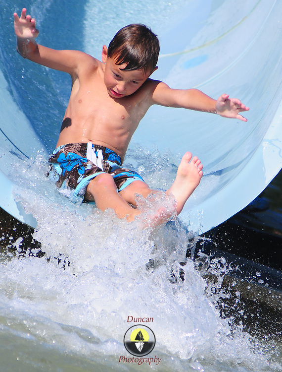 August 22, 2008 -- BRUNSWICK, Maine. Noah Dorr, 7, of Bath hits the water with gusto at the end of the Coffin Pond waterslide on Friday afternoon. Photo by Roger S. Duncan.