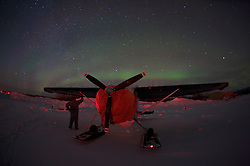 An airplane and pilot wait out the night beneath the northern lights in the Arctic Circle.