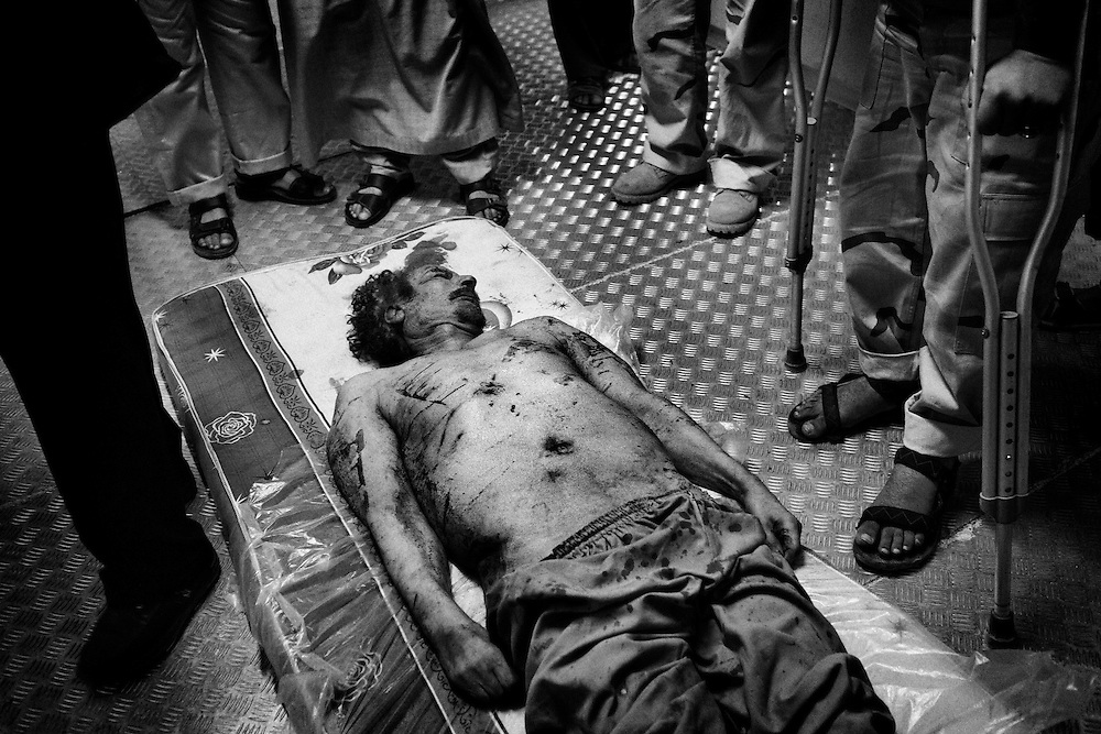 Libyan Rebels gather around the body of late leader Col. Muammar el-Qaddafi during a public visit to see his body, inside a refrigerator at a market in Misurata, Libya, on October 21, 2011. Photo by Mauricio Lima for The New York Times