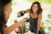 Two women at dinner party one pouring wine for other.