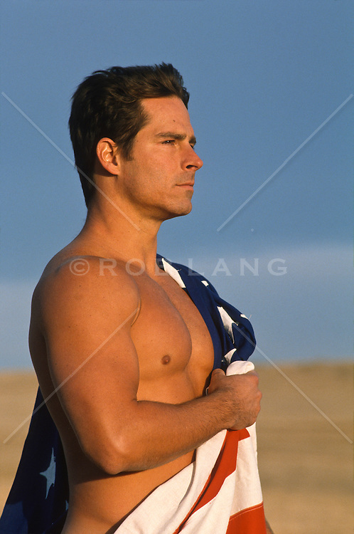 Profile of a shirtless young man wrapped in an American flag