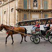 Horse drawn carriage and tour bus take tourists down different roads, Palermo, Sicily, Italy