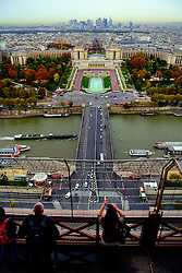 Tourists enjoying the view of Paris from the Eiffel Tower.