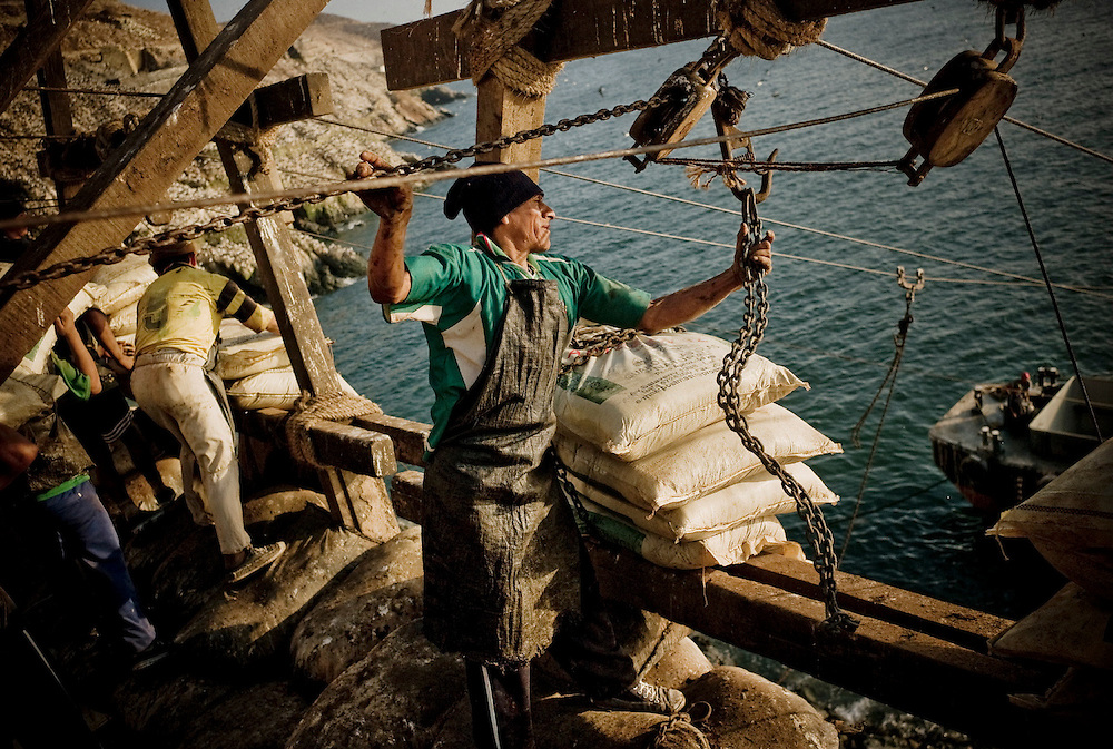 "A worker catches the chain to hang the sacks of guano as they load a ship from the ""cabria"" (installation from where the sacks of guano are loaded into ships only using gravity). Guañape Norte Island in the coast off Peru, April 2009."