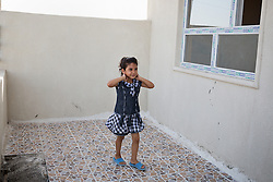 © Licensed to London News Pictures. Hamdaniyah, Iraq. 25/07/2014.  A young female Christian refugee from Mosul, stands in the garden of the home she now shares with the 16 other members of her extended family in Hamdaniyah, Iraq. She left Mosul on Friday the 18th of July when Islamic State fighters issued an ultimatum to the city's Christian community. When the family left they were forced to pay a tax for their car, and one member was threatened at knifepoint to ensure they handed over all of their possessions.<br /> <br /> <br /> Having taken over Mosul Iraq's second largest city in June 2014, fighter of the Islamic State (formerly known as ISIS) have systematically expelled the cities Christian population. Despite having been present in the city for more than 1600 years, Christians in the city were given just days to either convert to Islam, pay a tax for being Christian or leave; many of those that left were also robbed at gunpoint as they passed through Islamic State checkpoints.. Photo credit : Matt Cetti-Roberts/LNP