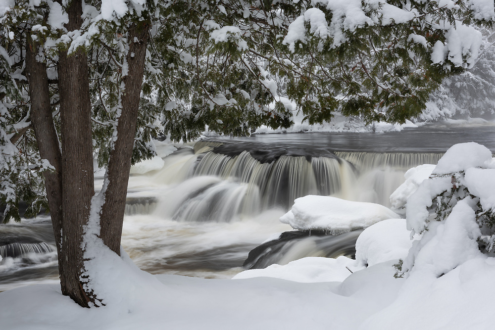 A blanket of fresh snow surrounds Upper Bond Falls in Michigan's Upper Peninsula.