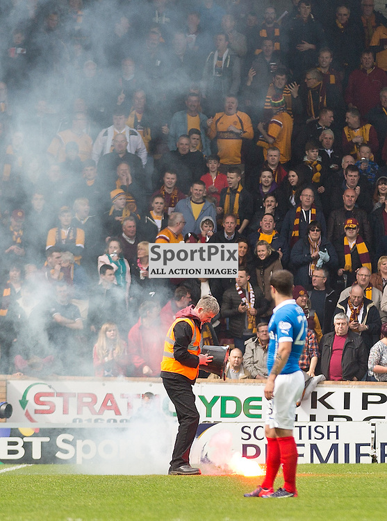 Motherwell v Rangers Scottish Premiership play-off final second leg 31 May 2015; A steward tries to put out a flare that's been thrown on to the pitch during the Motherwell v Rangers Scottish Premiership play-off final second leg match played at Fir Park Stadium, Motherwell;