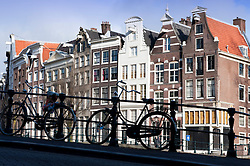Bicycle parked on bridge above canal in central Amsterdam Netherlands