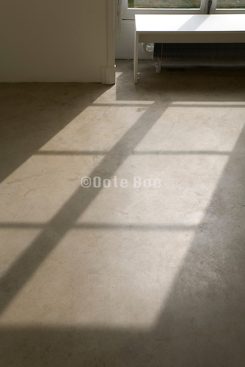 sunlight shining through a window on to a smooth concrete floor