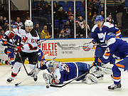 New York Islanders goalie Evgeni Nabokov (20) falls to the ice to push the  puck away from New Jersey Devils' Jaromir Jagr (68) as Islanders' Kyle Okposo (21) and Travis Hamonic (3) defend during an NHL hockey game on Saturday, March 1, 2014, in Uniondale, N.Y. (AP Photo/Kathy Kmonicek)