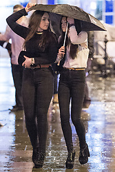 © Licensed to London News Pictures . 17/03/2013 . Manchester , UK . Two women share an umbrella in the rain . Evening revellers out in the rain and snow in to the early hours , in Manchester this St Patrick's Day morning (17th March) . Photo credit : Joel Goodman/LNP