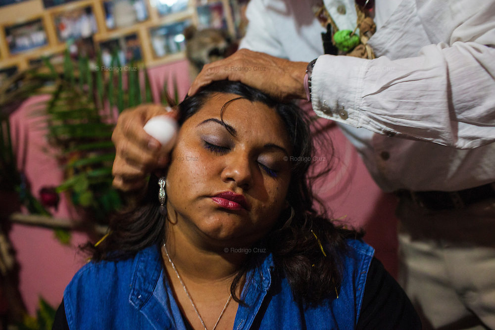 Luis Tomas Marthen Torres, a warlock, performs a ritual of protection to Julisa del Carmen in the town of Catemaco, Veracruz, Mexico, Oct. 19, 2011. In the midst of a violent streak in the state of Veracruz, witchery protection against extortion and help locating kidnapped kin have become the leading demands from clients, practitioners say. (Rodrigo Cruz/The New York Times)