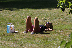 © Licensed to London News Pictures. 12/08/2016. LONDON, UK.  A woman sunbathes during the hot and sunny weather today in St James's Park in London.  Photo credit: Vickie Flores/LNP