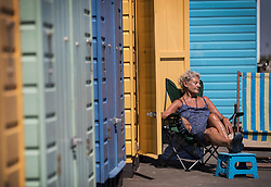 © Licensed to London News Pictures. 26/06/2018. Bournemouth, UK. A sun seeker relaxes in front of her beach hut in hot afternoon sunshine. Most of the UK is enjoying summer temperatures in the high 20's today. Photo credit: Peter Macdiarmid/LNP