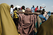 Aid organization workers gather people together to announce plans to relocate them to newer, better-serviced dwellings in the Ifo refugee camp in the Dadaab refugee complex in Kenya.
